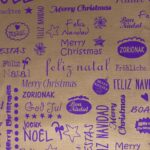 Bobina de papel de regalo de navidad cobre con mensaje multilenguaje violeta